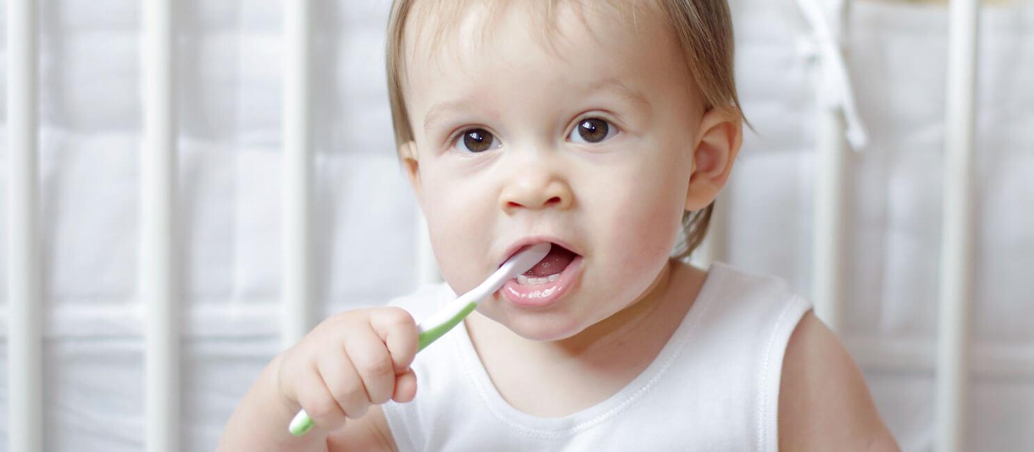 بنت صغيرة معها فرشاة اسنان خضراء
